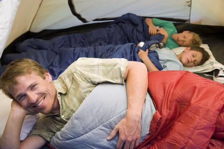 텐트에서 캠핑 가족, 어린이 (8-10) 백그라운드에서 자 고 아버지 전경, 웃 고, 세로에서 침낭에 휴식에 초점 스톡 콘텐츠