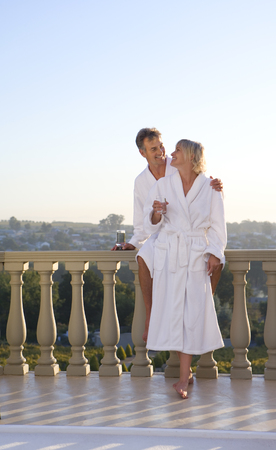 bath robes: Mature couple wearing white bath robes, standing on balcony, smiling at each other