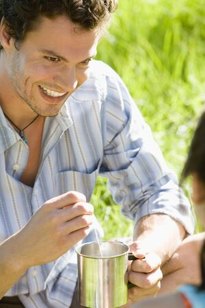 away from it all: Young couple sitting on grass, focus on man holding camping mug, smiling, close-up LANG_EVOIMAGES