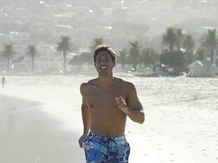 swimming shorts: South Africa, Cape Town, man in swimming shorts jogging along sandy beach, smiling, front view