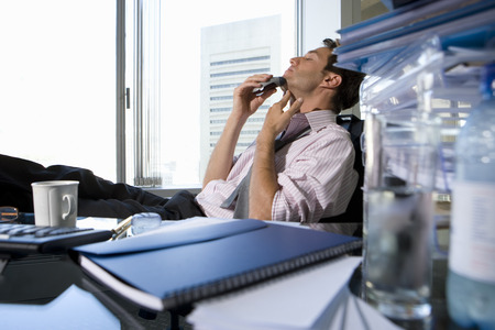 differential focus: Young businessman shaving at desk in office by book, mug and glass on desk (differential focus)