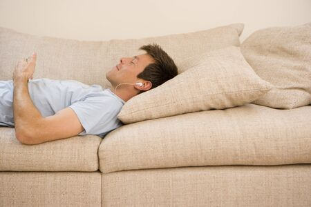 mp3 player: Man listening to mp3 player on sofa, eyes closed, side view