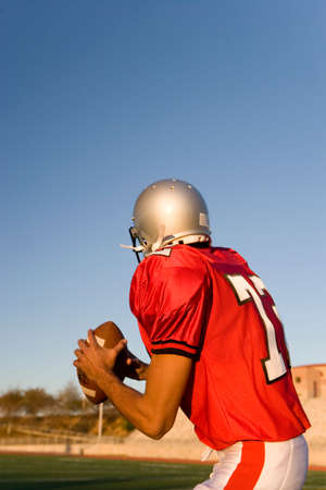 facing away: American football quarterback, in red strip, looking to throw ball during competitive game, rear view