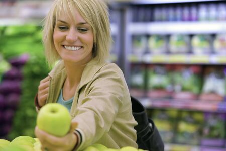 differential focus: Woman choosing green apple from display in supermarket, smiling (differential focus)
