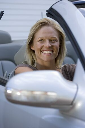 one mid adult woman only: Woman sitting in driving seat of parked convertible car on driveway, smiling, portrait LANG_EVOIMAGES