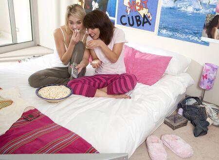pijamada: Dos adolescentes (15-17) sentado en la cama con las palomitas de ma�z, elevado vista