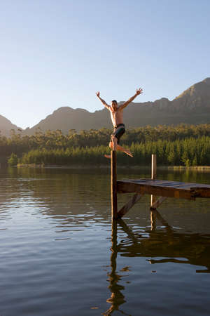 swimming shorts: Man, in swimming shorts, jumping from jetty into lake, arms up, showing off, smiling