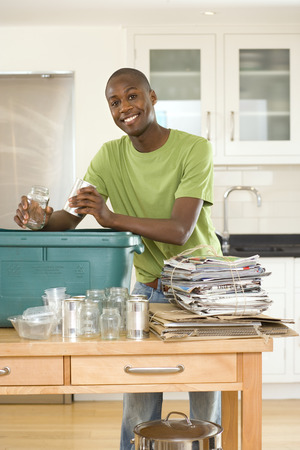 bundling: Young man putting empty glass jar and can into recycling bin in kitchen, smiling, portrait