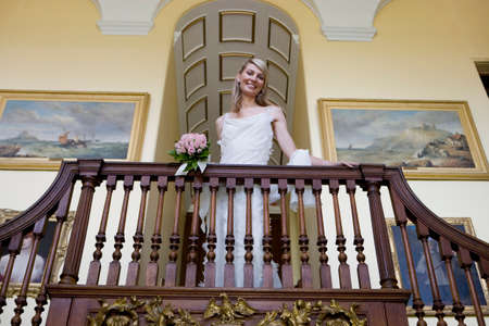 one mid adult woman only: Bride looking down from balcony at top of staircase, smiling, portrait, low angle view