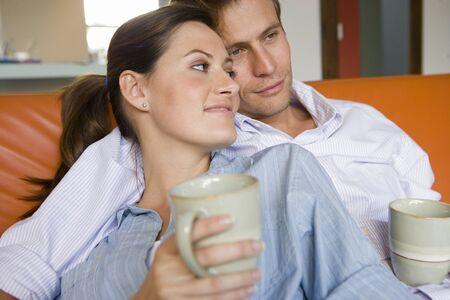 amigos abrazandose: Pareja sentados juntos en el sof�, sosteniendo tazas, sonriente, primer plano LANG_EVOIMAGES