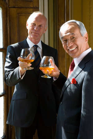 Senior businessman and colleague with drinks, smiling, portrait Stock Photo