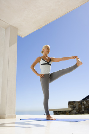 only mid adult women: Mature woman in standing yoga position on exercise mat outdoors, low angle view LANG_EVOIMAGES