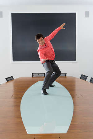 pretending: Businessman pretending to surf on conference table, smiling, portrait