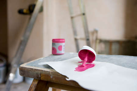 undecorated: Small tin of pink paint and paintbrush on paper in undecorated room, close-up, focus on foreground LANG_EVOIMAGES