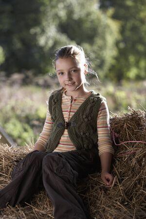 elementary age girls: Girl (9-11) sitting on hay, smiling, portrait LANG_EVOIMAGES