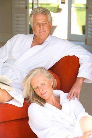 bath robes: Mature couple wearing white bath robes, woman sitting on floor by man with book on sofa