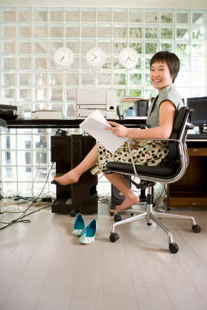 barefooted: Young barefooted woman sitting in office, holding paperwork, smiling, portrait