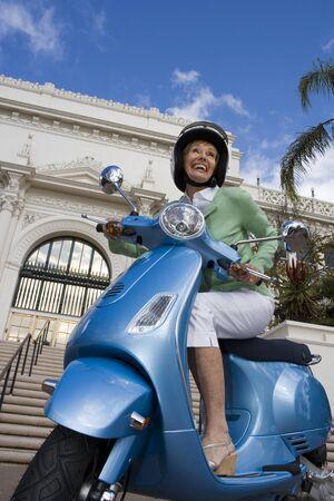 tilt view: USA, California, San Diego, Balboa Park, senior woman riding on blue motor scooter, smiling, side view, low angle view (tilt)