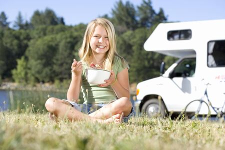 motor home: Girl (9-11) eating from bowl on grass with legs crossed, motor home in background, smiling, portrait