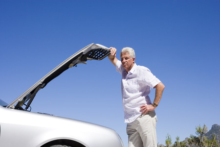 engine bonnet: Senior man experiencing car trouble, looking at engine, leaning against open bonnet, thinking LANG_EVOIMAGES
