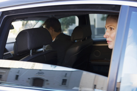 only mid adult men: Businesswoman sitting in back-seat of chauffeur driven car, looking out of open window, side view