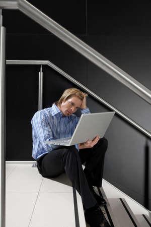 only one mid adult man: Businessman sitting on staircase, using laptop in lap, leaning head on hand, thinking, side view LANG_EVOIMAGES