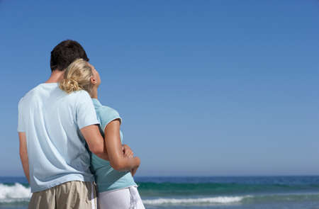 hugging couple: Couple standing on beach, looking at horizon over sea, man embracing woman, rear view LANG_EVOIMAGES