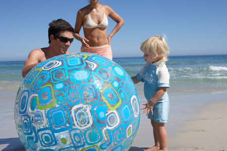 two generation family: Two generation family playing with large turquoise beach ball, sea in background LANG_EVOIMAGES