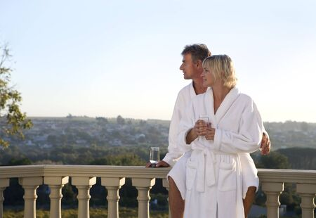 bath robes: Mature couple wearing white bath robes, standing on balcony, embracing