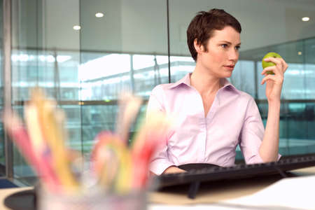 differential: Businesswoman sitting at desk in office, holding green apple, daydreaming (differential focus)