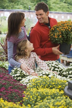two generation family: Two generation family shopping for flowers in garden centre, man holding pot plant, smiling LANG_EVOIMAGES