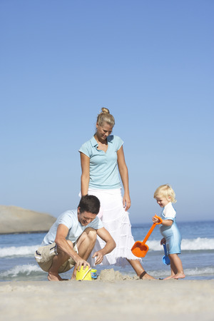 two generation family: Two generation family playing with bucket and spade on sandy beach, sea in background