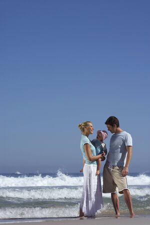 two generation family: Two generation family standing on beach at waters edge, mother holding daughter (2-4)