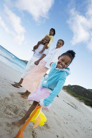 two generation family: Two generation family standing on beach, holding hands, smiling, side view, portrait (tilt)