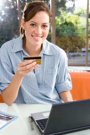 one mid adult woman only: Woman holding credit card by laptop, smiling, portrait