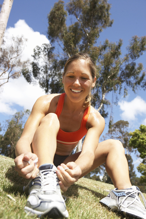 knotting: Woman tying trainer shoelace in park, sitting on grass, smiling, close-up, surface level (tilt) LANG_EVOIMAGES