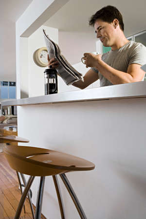 angle bar: Man sitting at breakfast bar in kitchen with cafetiere and mug, reading newspaper, low angle view