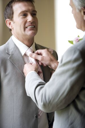 Father adjusting grooms tie, smiling, low angle view