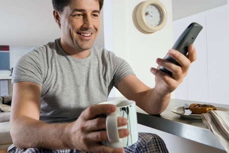 one mid adult man only: Man sitting at breakfast bar in kitchen, holding mug and cordless phone, smiling, close-up LANG_EVOIMAGES