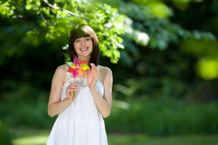 pinwheel: Young woman with pinwheel outdoors, smiling, portrait LANG_EVOIMAGES
