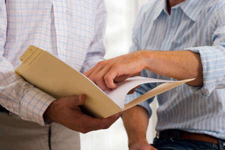 midsection: Two businessmen looking at document in file, close-up, mid-section LANG_EVOIMAGES