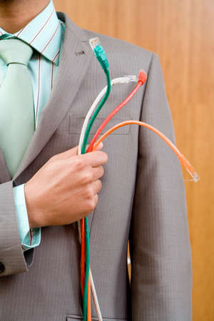 mid section: Businessman holding cables to chest, mid section LANG_EVOIMAGES