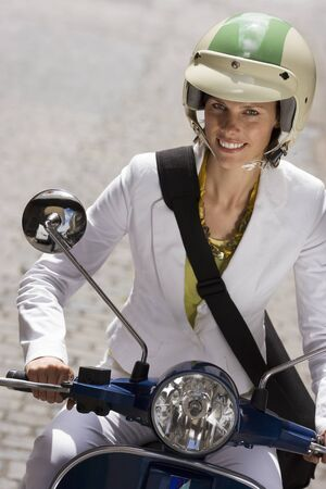 crash helmet: Woman in crash helmet riding on scooter in street, smiling, front view, close-up (tilt)