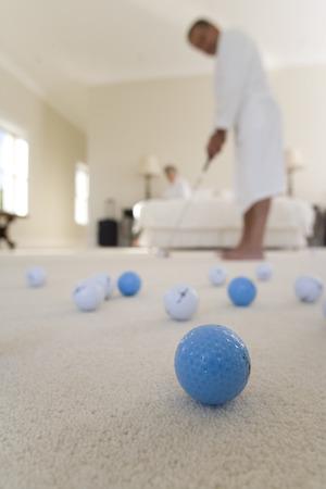 putt: Senior couple in bedroom, man practising golf putt, focus on golf balls in foreground