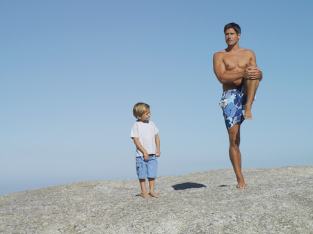 swimming shorts: Father and son (4-6) playing on rock near beach, smiling, man in swimming shorts standing on one leg LANG_EVOIMAGES