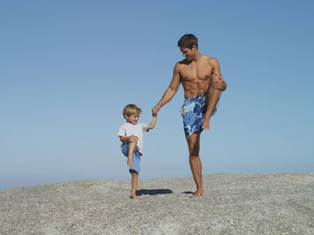swimming shorts: Father and son (4-6) playing on rock, standing on one leg, smiling, man in swimming shorts LANG_EVOIMAGES