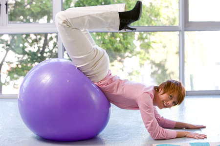 out of context: Young woman on exercise ball, forearms on floor, legs in air, smiling, side view LANG_EVOIMAGES
