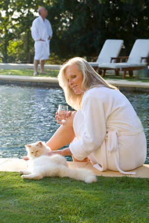 bath robes: Mature couple wearing white bath robes by swimming pool, woman smiling at cat in foreground LANG_EVOIMAGES