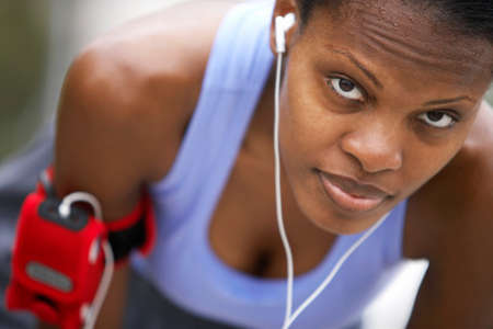 differential focus: Exhausted female jogger wearing sports vest, leaning forwards, listening to MP3 player strapped to arm, close-up, portrait (differential focus) LANG_EVOIMAGES