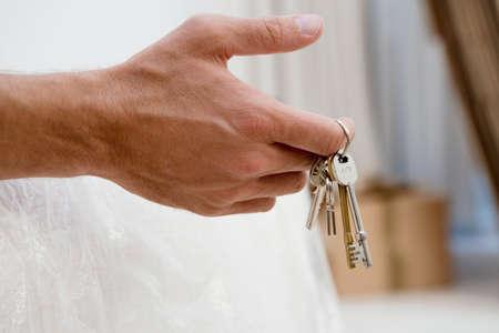 side keys: Man holding set of keys, close-up of hand, side view